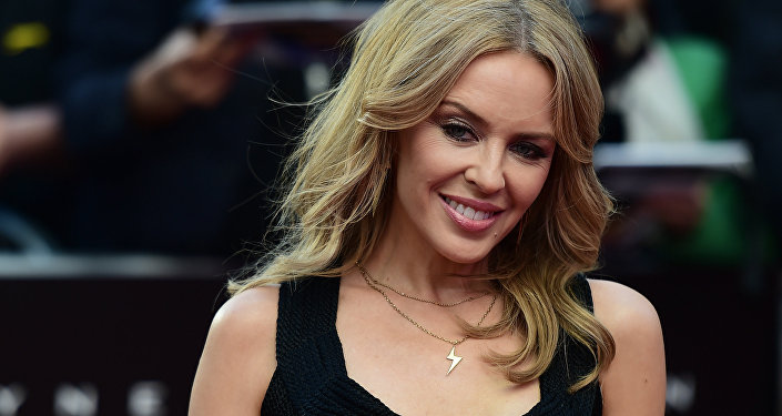 Australian singer Kylie Minogue poses on the carpet as she arrives to attend the World premiere of the film 'San Andreas' in London on May 21, 2015