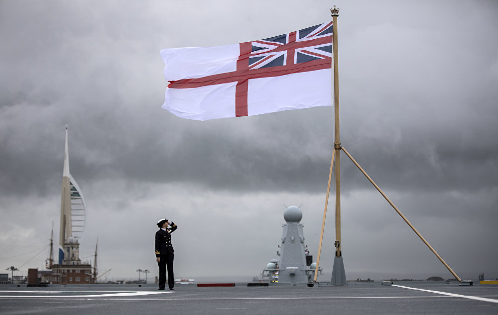 A naval officer looks up at the white ensign flying at the stern of the aircraft carrier HMS Queen Elizabeth, which has been beset with technical problems