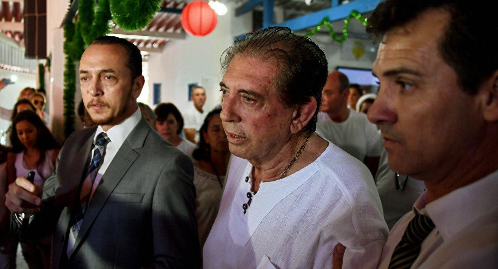 Brazilian spiritual healer Joao Teixeira de Faria (C), known as Joao de Deus (John of God) is escorted by supporters, upon arrival at his healing center Casa de Dom Inacio de Loyola, in Abadiania, 120 km southwest of Brasilia, state of Goias on December 12, 2018.