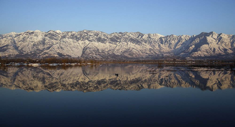 snow-capped mountains are reflected in the Himalayan region of Kashmir on the border between India and Pakistan