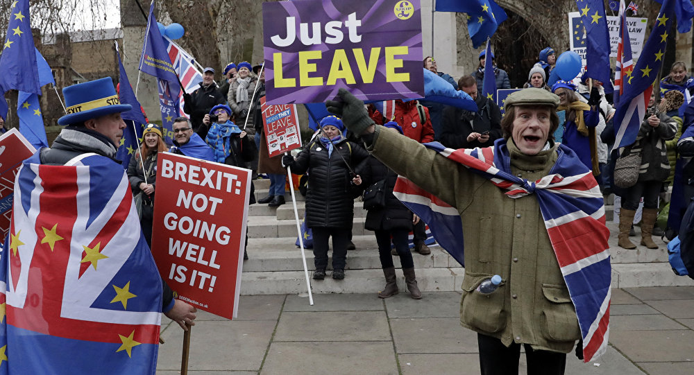 A pro-leave supporter, right, hods a placard in front of a group of pro-remain supporters during demonstrations in London, Tuesday, Jan. 29, 2019. Britain's Parliament is set to vote on competing Brexit plans, with Prime Minister Theresa May desperately seeking a mandate from lawmakers to help secure concessions from the European Union.