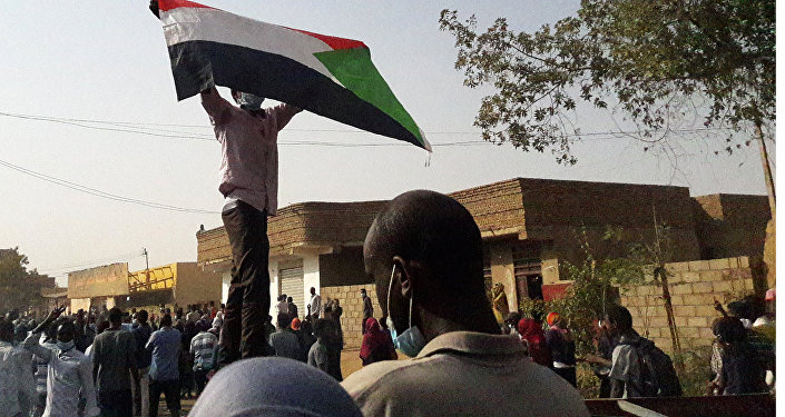 Demonstrators against President al-Bashir hold up a Sudanese flag during protests in Omdurman in January 2019