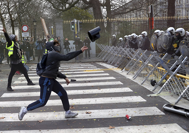 A protestor throws an object at a police line during a demonstration in Brussels, Saturday, Dec. 8, 2018.