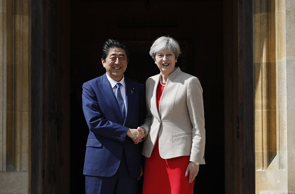 Britain's Prime Minister Theresa May (R) welcomes Japan's Prime Minister Shinzo Abe (L) at Chequers, the prime minister's official country residence, near Ellesborough, northwest of London, on April 28, 2017