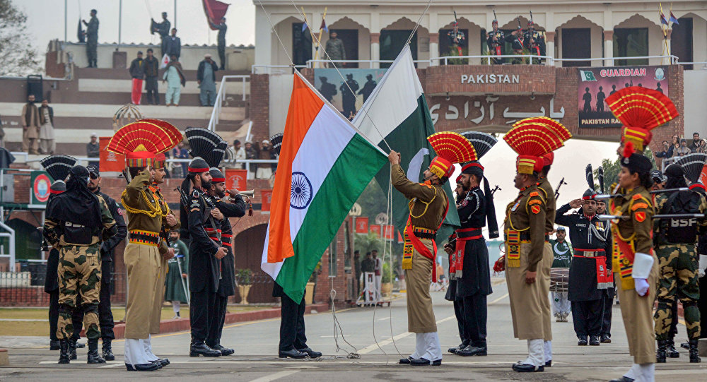 Indian Border Security Force personnel wearing brown uniforms and Pakistani Rangers wearing black uniforms take part in the Beating Retreat ceremony at the India-Pakistan Wagah-Attari border post, some 35 kms from Amritsar on January 22, 2019