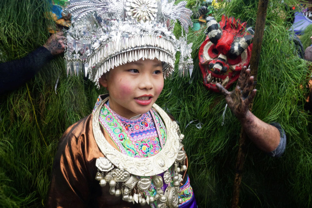 Ethnic Miao Woman Poses with Ethnic Miao Men Dressed as Manghao