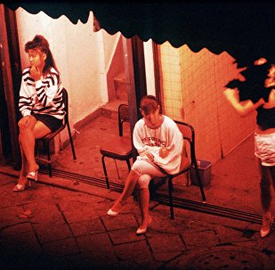 Prostitutes wait for customers outside a brothel