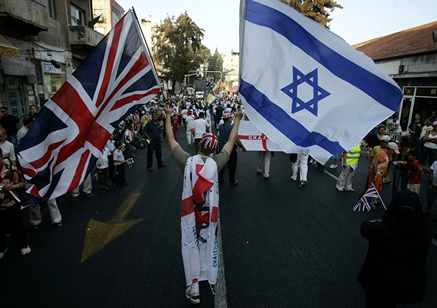 A Christian Evangelical from the United Kingdom waves Israeli and British flags during a parade in celebration of the Jewish holiday of Sukkoth, in downtown Jerusalem, 02 October 2007