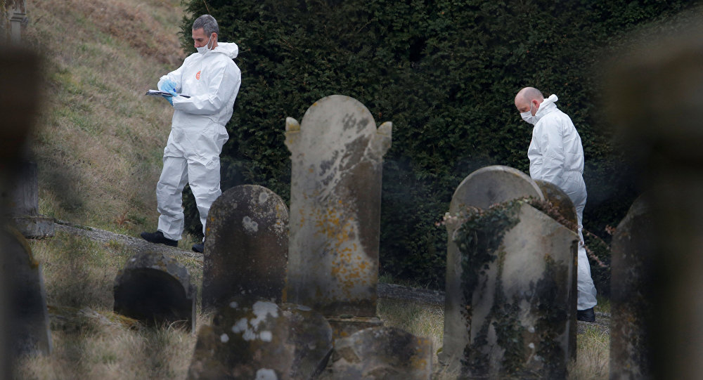 French gendarmes conduct their investigation as they examine graves that were desecrated with swastikas in the Jewish cemetery in Quatzenheim, near Strasbourg, France, February 19, 2019