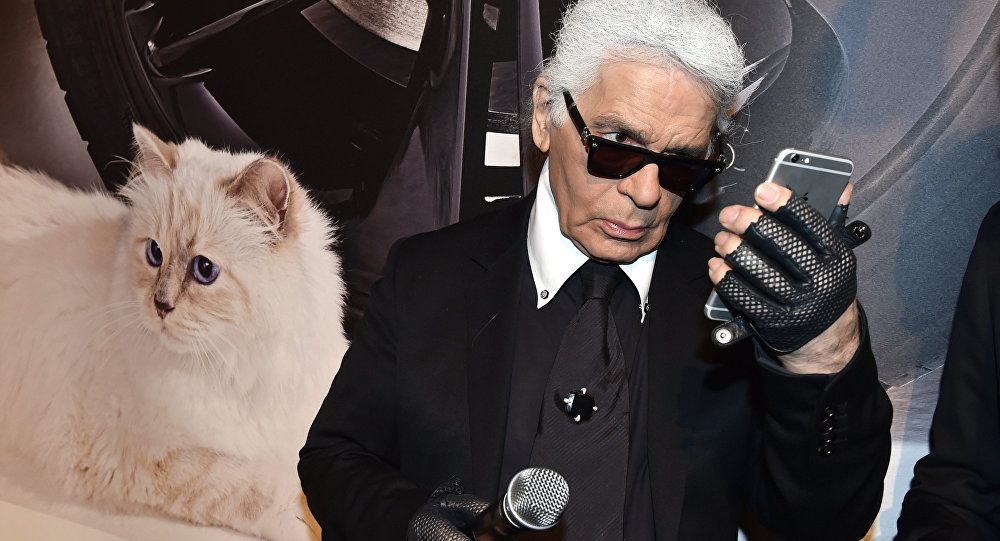 German fashion designer, artist, and photographer Karl Lagerfeld poses next to a photo of his cat Choupette during the inauguration of the show Corsa Karl and Choupette at the Palazzo Italia in Berlin on February 3, 2015
