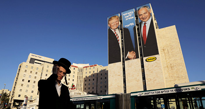 A man walks past a Likud election campaign billboard, depicting U.S. President Donald Trump shaking hands with Israeli Prime Minister Benjamin Netanyahu, in Jerusalem February 4, 2019