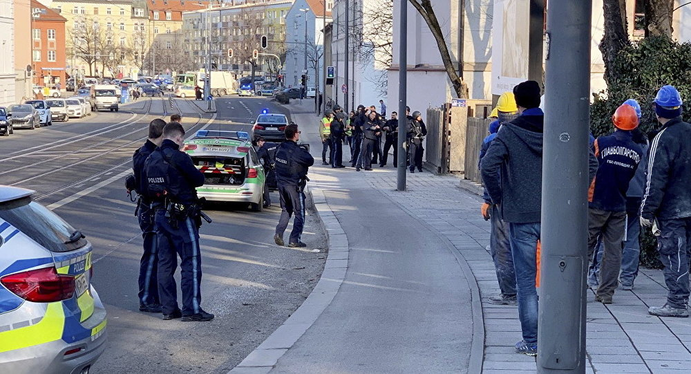 Police officers observe a crime scene in Munich, Germany, Thursday, Feb. 21, 2019