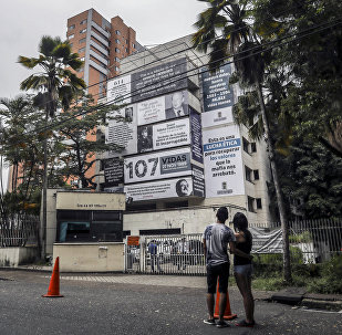 A couple looks at the Monaco building, which was once home to Colombian drug lord Pablo Escobar, as it is covered with pictures of victims of his Medellin Cartel, in Medellin, Colombia, on December 11, 2018