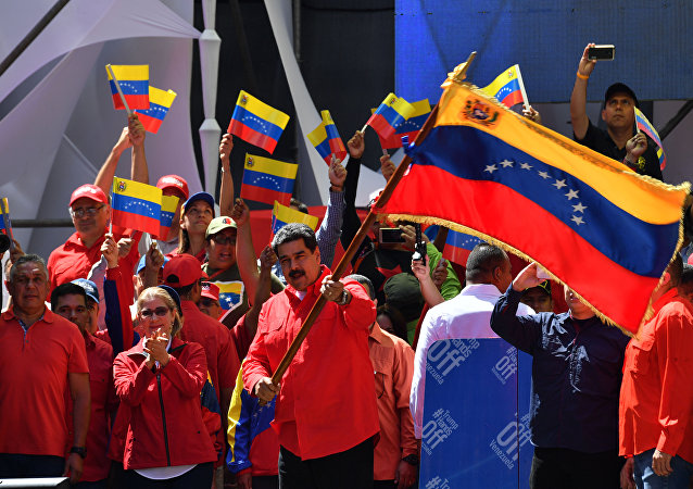 Venezuelan President Nicolas Maduro (C) waves the national flag during a pro-government march in Caracas, on February 23, 2019.