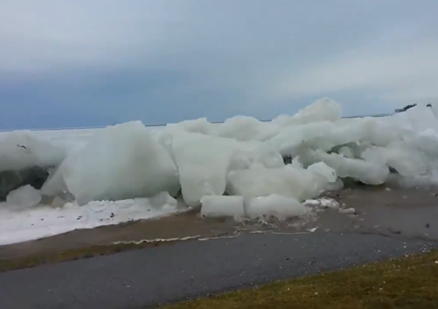 'Ice Tsunami' makes its way past a retaining wall and onto a roadway in Fort Erie, Canada.