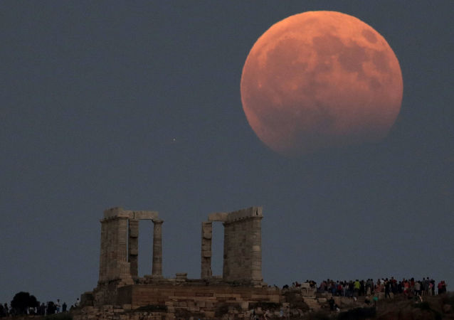 Temple of Poseidon is seen as a full moon is partially covered by the Earth's shadow during a lunar eclipse in Cape Sounion, east of Athens, Greece, August 7, 2017.