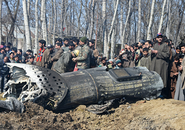 Indian soldiers and Kashmiri onlookers stand near the remains of an Indian Air Force aircraft after it crashed in Budgam district, on the outskirts of Srinagar on February 27, 2019