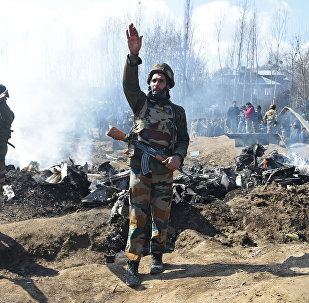 Indian soldiers gesture near the remains of an Indian Air Force aircraft after it crashed in Budgam district, some 30 kms from Srinagar on February 27, 2019
