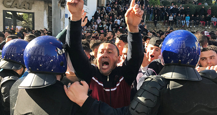 A man gestures and shouts near riot police during a protest against President Abdelaziz Bouteflika's plan to extend his 20-year rule by seeking a fifth term in April elections in Algiers, Algeria, March 1, 2019.