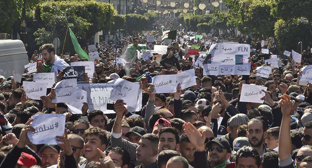 Algerians march with protest sings reading peaceful, and leave means leave in Arabic, during a rally against ailing President Abdelaziz Bouteflika's bid for a fifth term in power, in the capital Algiers on March 1, 2019.