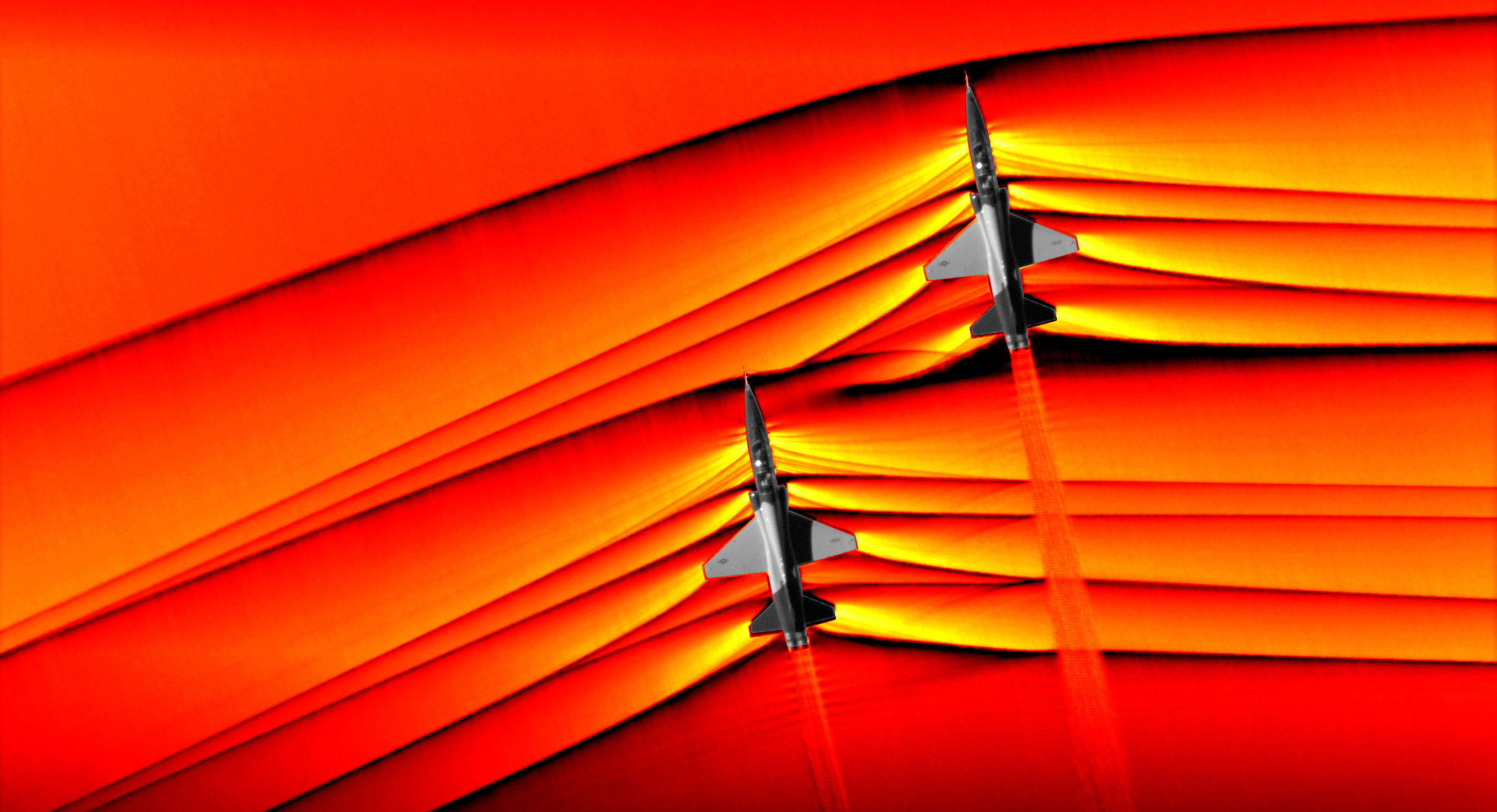 Using the schlieren photography technique, NASA was able to capture the first air-to-air images of the interaction of shockwaves from two supersonic aircraft flying in formation. These two U.S. Air Force Test Pilot School T-38 aircraft are flying in formation, approximately 30 feet apart, at supersonic speeds, or faster than the speed of sound, producing shockwaves that are typically heard on the ground as a sonic boom. The images, originally monochromatic and shown here as colorized composite images, were captured during a supersonic flight series flown, in part, to better understand how shocks interact with aircraft plumes, as well as with each other.