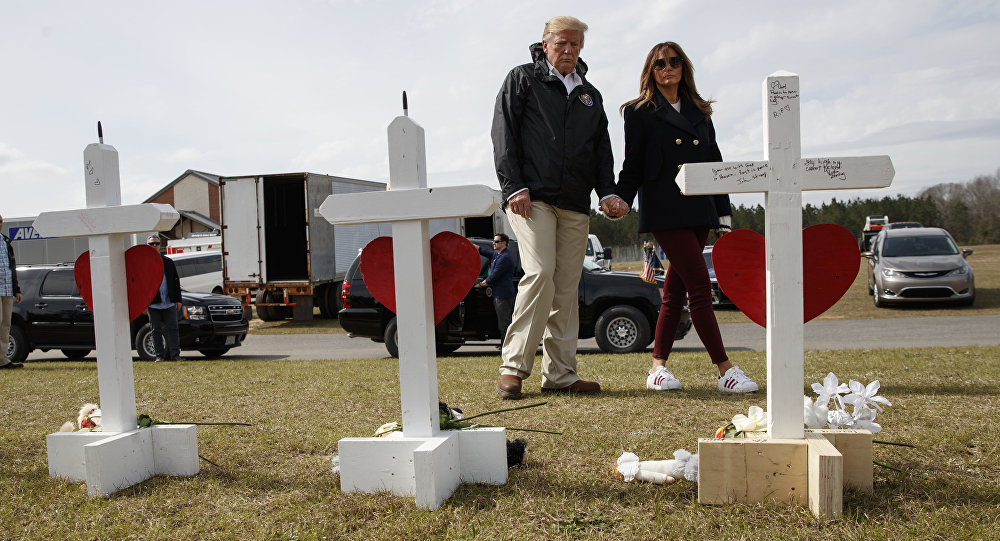 President Donald Trump and first lady Melania Trump visit a line of crosses at Providence Baptist Church in Smiths Station, Ala., Friday, March 8, 2019, as they tour areas where tornados killed 23 people in Lee County, Alabama