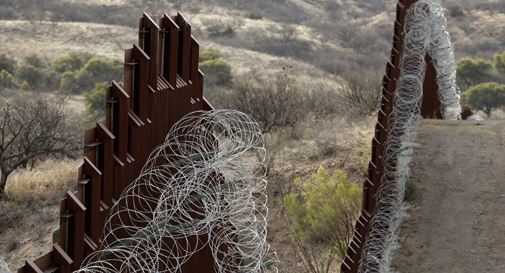 A razor-wire-covered border wall separates the United States, at left, from Mexico east of Nogales, Ariz