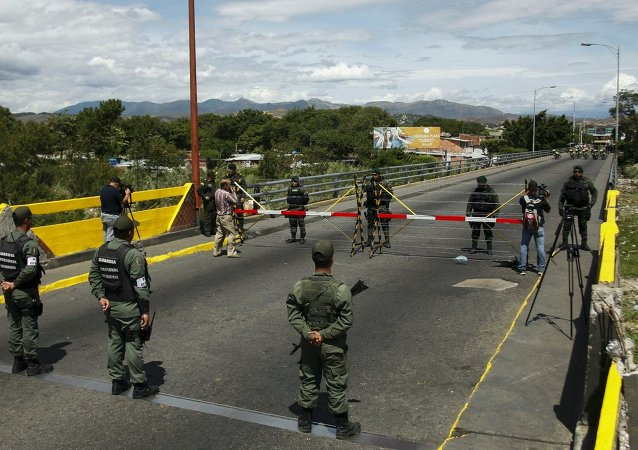 Venezuela's National Guards (bottom) stand in front of Colombia's soldiers at Simon Bolivar international bridge, on the border with Colombia