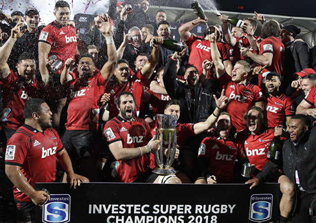 Crusaders players celebrate with their trophy after defeating the Lions 37-18 to win Super Rugby final in Christchurch, New Zealand, Saturday, Aug. 4, 2018