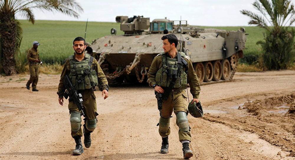Israeli soldiers walk by an armoured personnel carrier (APC) near the border between Israel and Gaza on its Israeli side, March 15, 2019