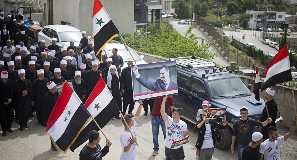 Druze men carry Syrian flags and pictures of Syrian President Bashar Assad during a rally marking Syria's Independence Day, in the Druze village of Ein Qiniyye, Israeli-controlled Golan Heights, Tuesday, April 17, 2018.