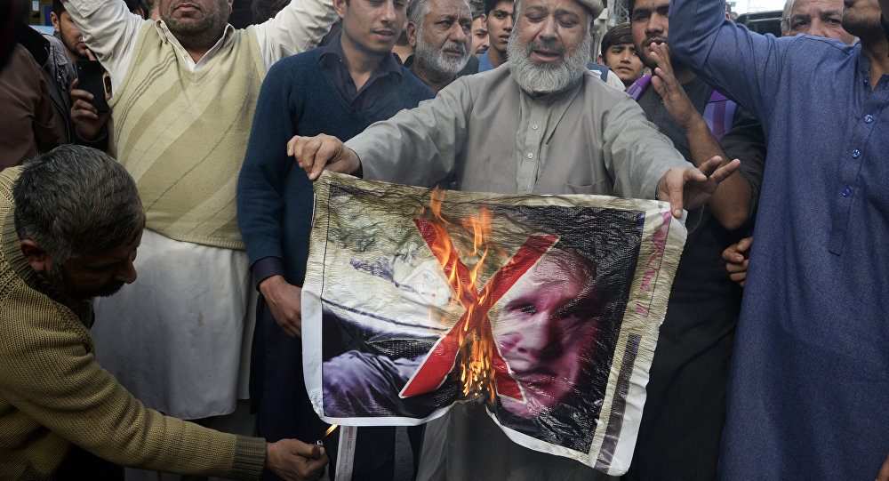 Pakistan traders burn a poster with the image of Brenton Tarrant, the man charged in relation against the March 15 attack on two mosques in Christchurch, during a protest in Peshawar on March 16, 2019