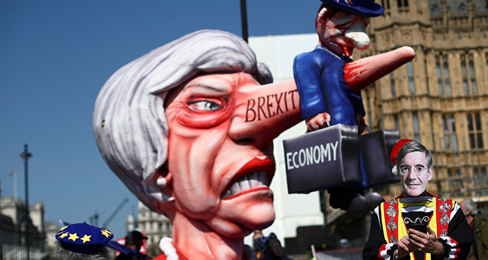 A man wearing a mask of Britain's Conservative Party MP Jacob Rees-Mogg is pictured next to anti-Brexit protesters outside the Houses of Parliament in London, Britain April 1, 2019