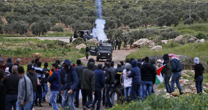 Palestinian protesters face Israeli troops during clashes following a demonstration in the village of Mughayir in the Israeli-occupied West Bank