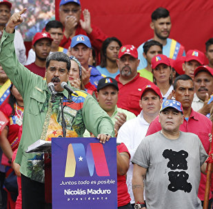 Argentina's former star player Diego Armando Maradona, right, listens to Venezuela's President Nicolas Maduro speaking during his closing campaign rally in Caracas, Venezuela, Thursday, May 17, 2018