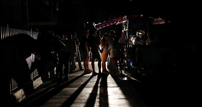 Locals gather at a street food cart during a blackout in Caracas Venezuela