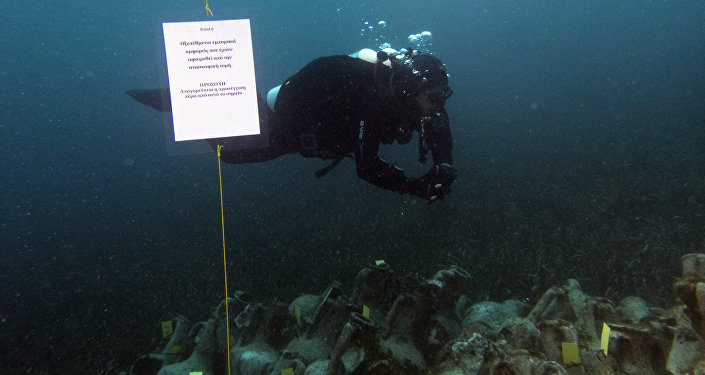 In this photo taken on Sunday, April 7, 2019, an archaeologists dives next ancient amphoras from a 5th Century B.C. shipwreck, the first ancient shipwreck to be opened to the public in Greece, including to recreational divers who will be able to visit the wreck itself, near the coast of Peristera, Greece.