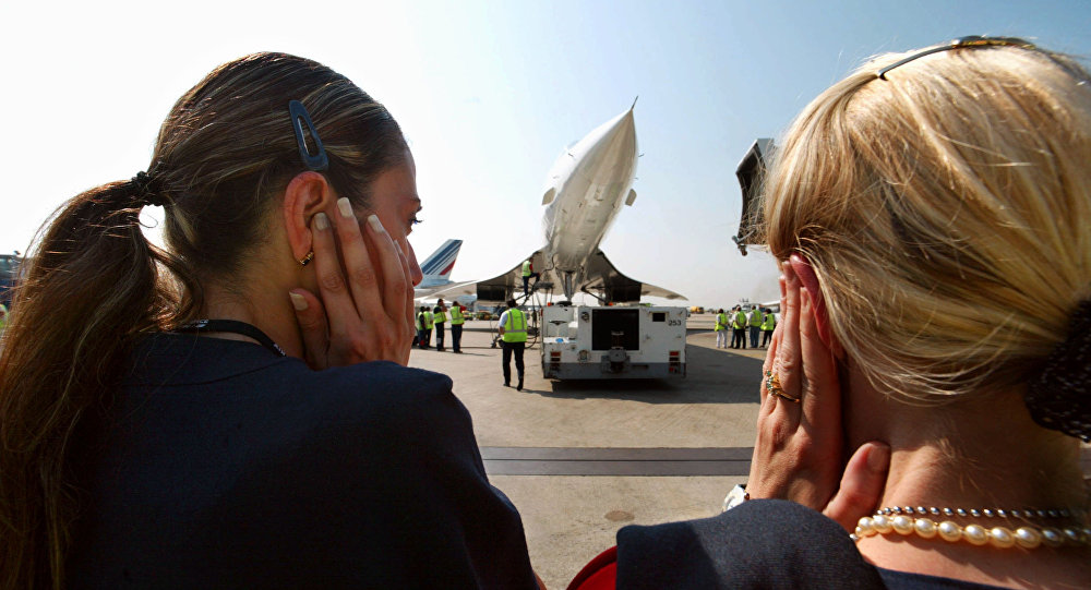Crew's members of the last Air France Concorde flight to New York protect their ears during a motor check up before the takeoff 30 May 2003 at Charles de Gaulle airport outside Paris