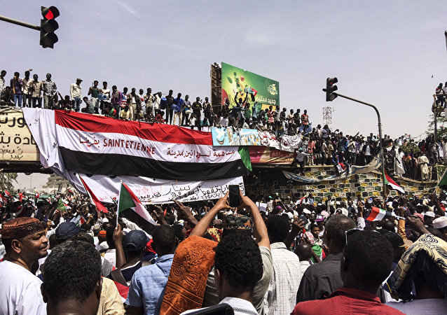 Demonstrators gather in Sudan's capital of Khartoum, Friday, April 12, 2019. The Sudanese protest movement has rejected the military's declaration that it has no ambitions to hold the reins of power for long after ousting the president of 30 years, Omar al-Bashir. The writing on the Sudanese flag says With the participation of the Sudanese in Saint Etienne, France.
