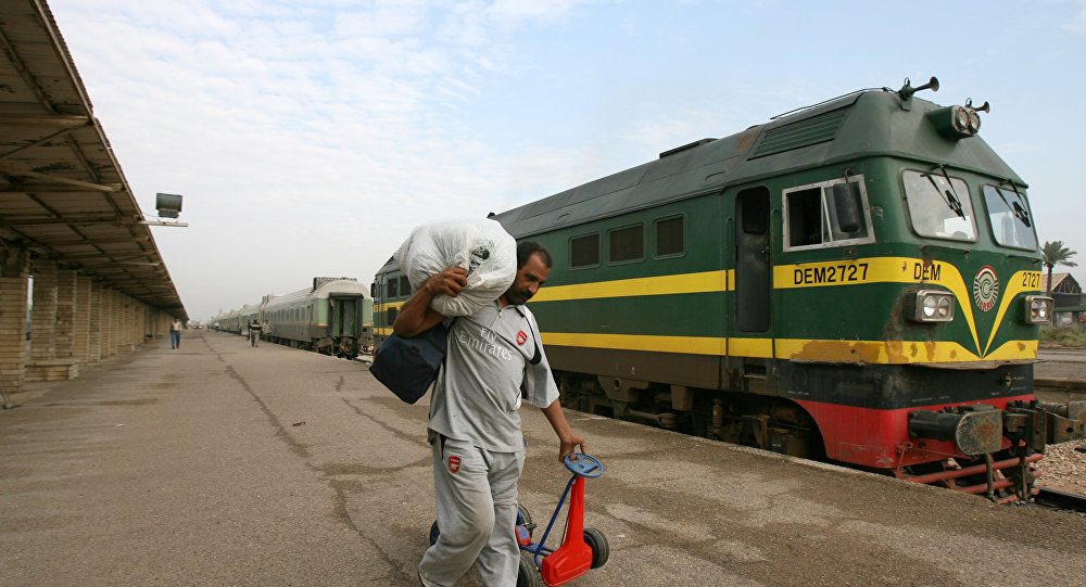 An Iraqi passenger carries his belongings next to a train at the al-Alawi railway station, central Baghdad, Iraq