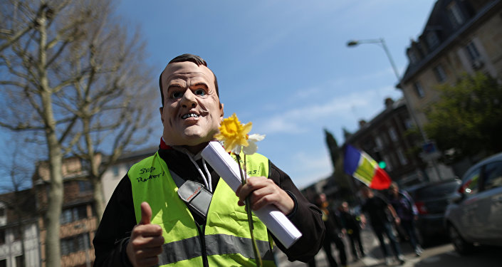 A demonstrator sporting a mask representing French President Emmanuel Macron holds a yellow flower during yellow vest protests, in Rouen on April 6, 2019