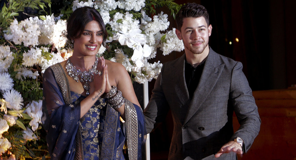 Bollywood actress Priyanka Chopra and musician Nick Jonas pose for photographs at their wedding reception in Mumbai, India, Wednesday, Dec 19, 2018