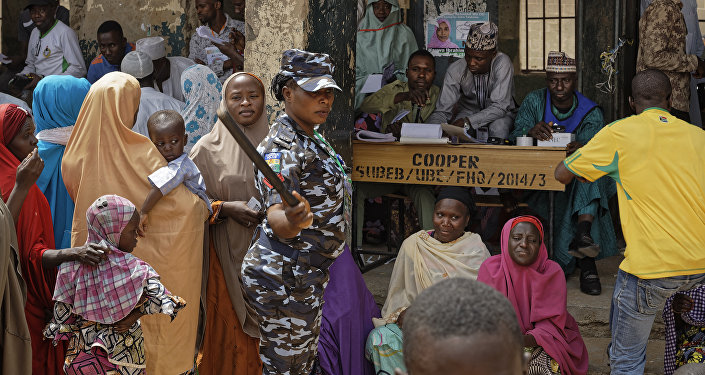 A policewoman chases away children as women queue in the midday sun to cast their votes at a polling station in Kano, northern Nigeria Saturday, Feb. 23, 2019. Nigerians are going to the polls for a presidential election Saturday, one week after a surprise delay for Africa's largest democracy.