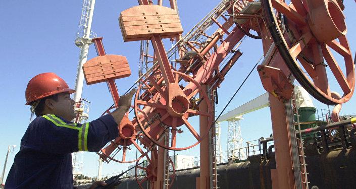 Jeaniel Jimenez directs another worker before loading an oil tanker at the Jose refinery in eastern Puerto la Cruz, about 300 kilometers, 186 miles of Caracas, Venezuela. File photo