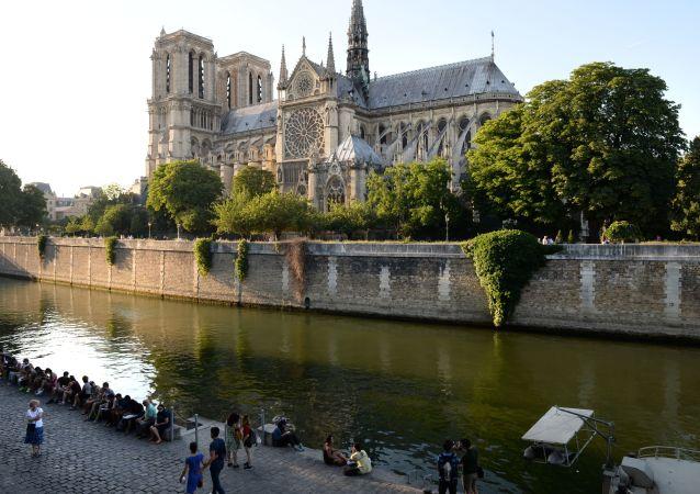 Отдыхающие на набережной Сены у Собора Парижской Богоматери (Notre-Dame de Paris) в Париже