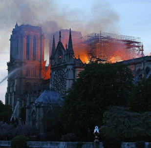 A firefighter tackles the blaze as flames and smoke rise from Notre Dame cathedral as it burns in Paris, Monday, April 15, 2019. Massive plumes of yellow brown smoke is filling the air above Notre Dame Cathedral and ash is falling on tourists and others around the island that marks the center of Paris