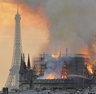 In this image made available on Tuesday April 16, 2019 flames and smoke rise from the blaze after the spire toppled over on Notre Dame cathedral in Paris, Monday, April 15, 2019