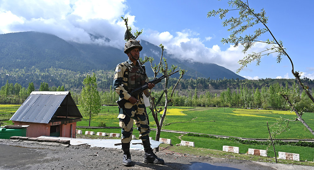 An Indian Border Security Force (BSF) soldier stands guard on the top of a polling station during a second phase of elections at Kangan, some 35 km from Srinagar on April 18, 2019