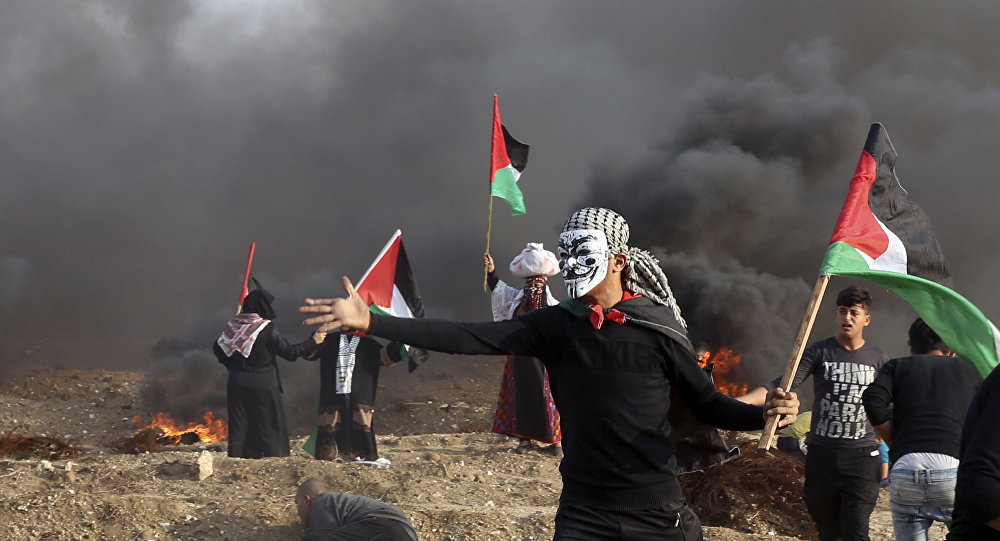Protesters wave their national flags while others burn tires near the fence of Gaza Strip border with Israel during a protest east of Gaza City, Friday, Nov. 9, 2018