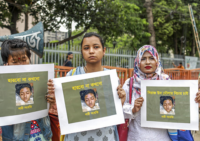 In this photo taken on April 12, 2019 Bangladeshi women hold placards and photographs of schoolgirl Nusrat Jahan Rafi at a protest in Dhaka, following her murder by being set on fire after she had reported a sexual assault
